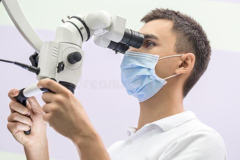 Доктор используя зубоврачебный микроскоп стоковое изображение