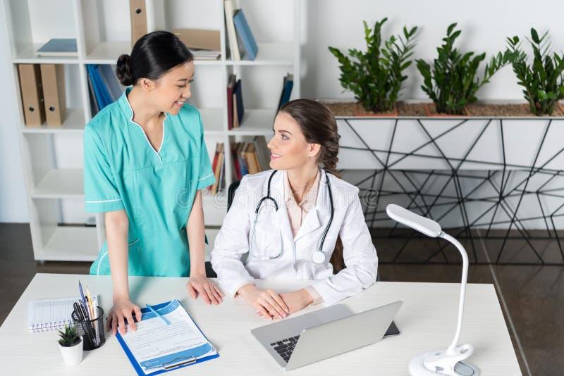 Доктор используя компьтер-книжку и разговаривающ с молодым азиатским internist в клинике стоковое фото rf