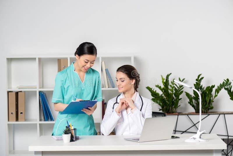 Доктор используя компьтер-книжку и разговаривающ с молодым азиатским сочинительством internist в доске сзажимом для бумаги в клин стоковая фотография rf