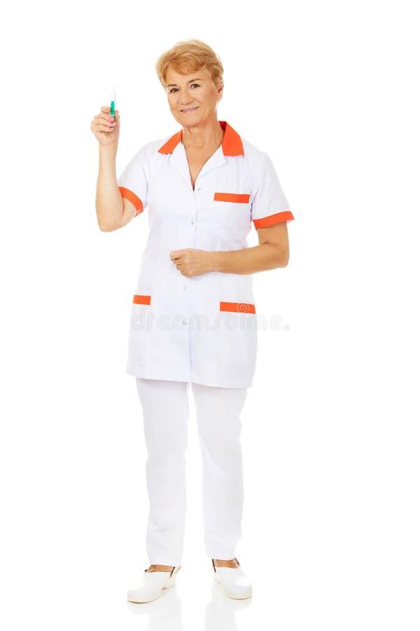Доктор или медсестра улыбки пожилые женские держат шприц стоковые фотографии rf