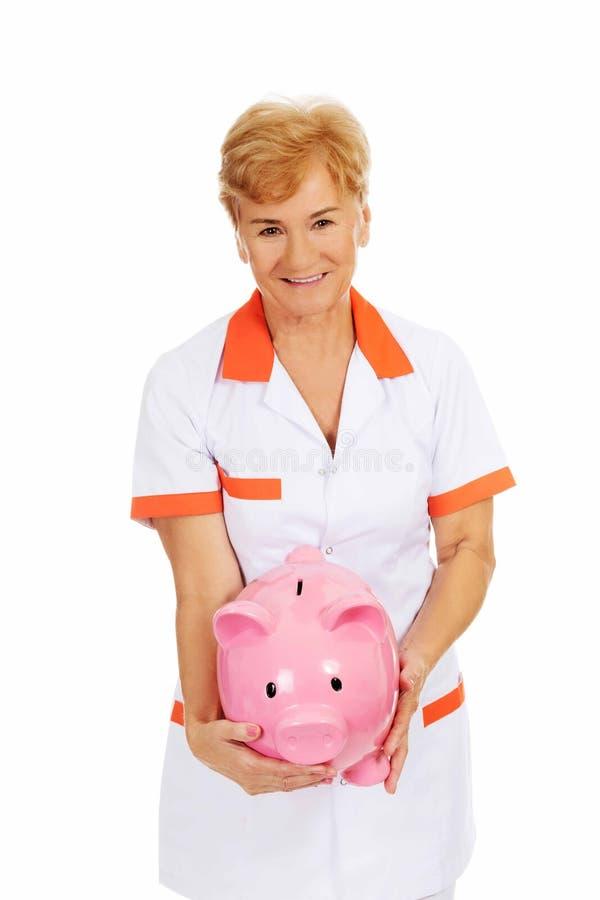 Доктор или медсестра улыбки пожилые женские держа piggybank стоковое фото rf