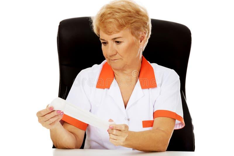 Доктор или медсестра улыбки пожилые женские сидя за столом и повязкой владениями стоковое фото rf