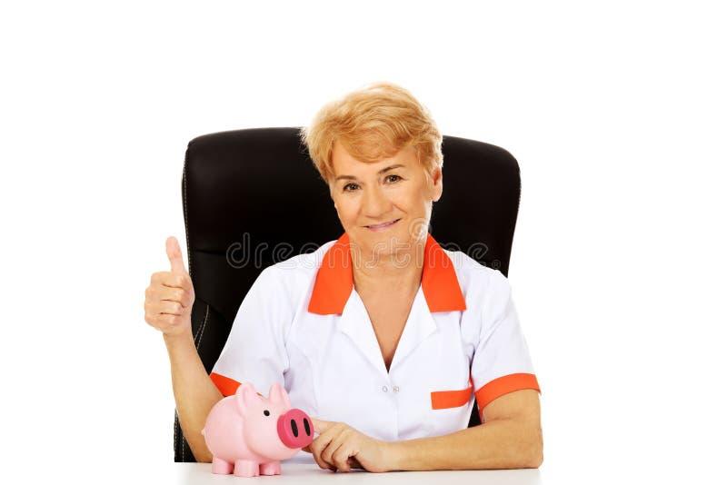 Доктор или медсестра улыбки пожилые женские сидя за столом с piggybank стоковая фотография rf