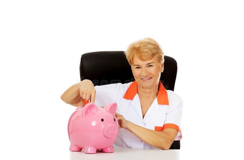 Доктор или медсестра улыбки пожилые женские сидя за piggybank острословия стола стоковые фото