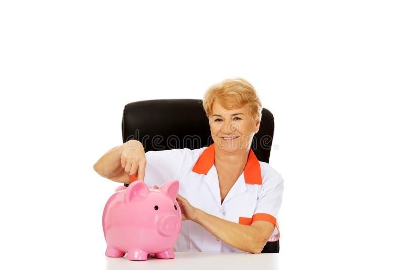 Доктор или медсестра улыбки пожилые женские сидя за piggybank острословия стола стоковые фотографии rf