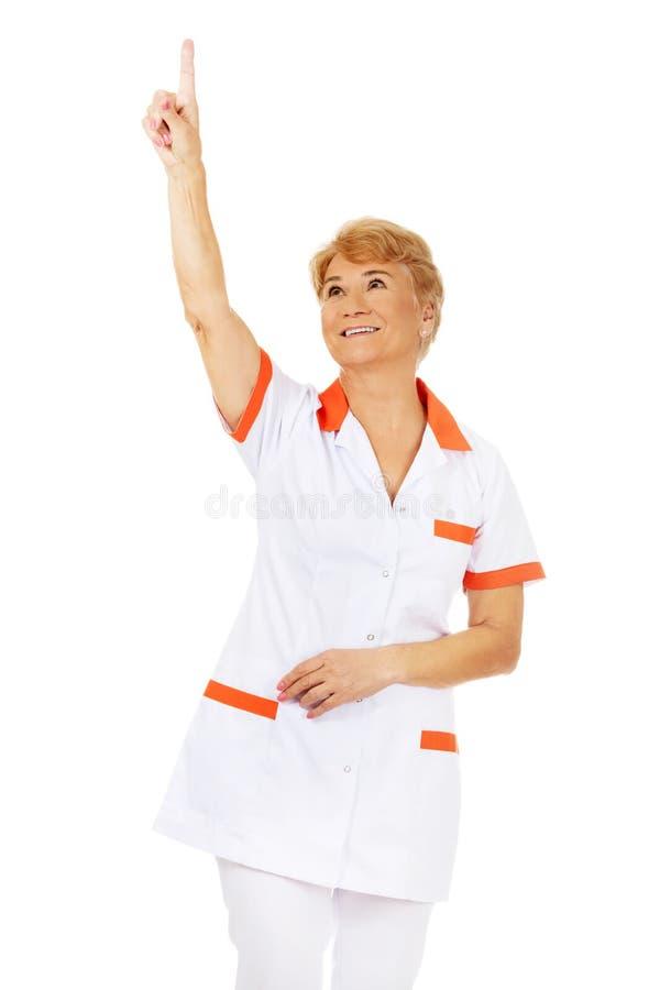 Доктор или медсестра улыбки пожилые женские указывая вверх стоковое фото rf