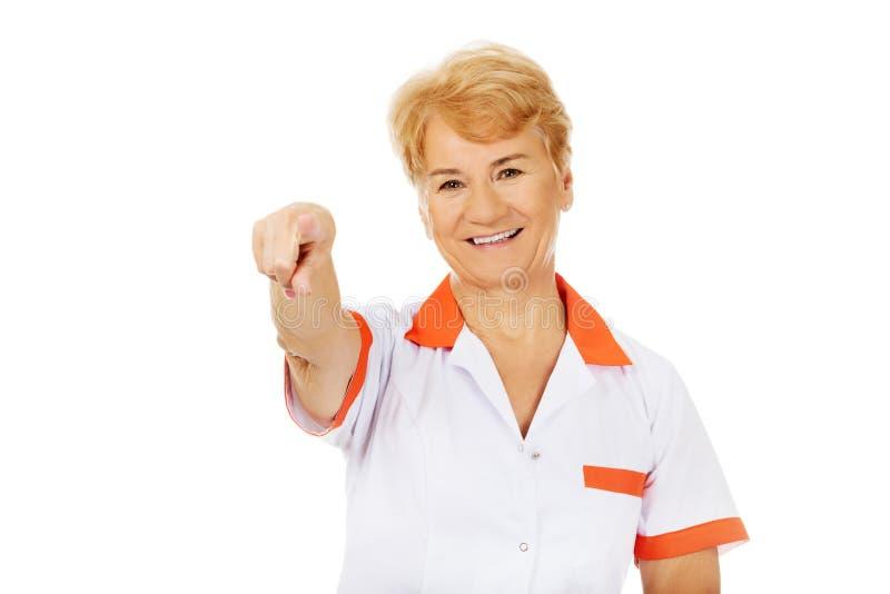 Доктор или медсестра улыбки пожилые женские указывая на камеру стоковые фотографии rf