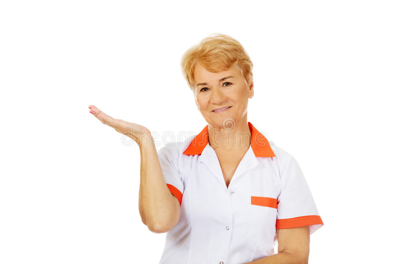Доктор или медсестра улыбки пожилые женские preseting что-то на открытой ладони стоковые фотографии rf