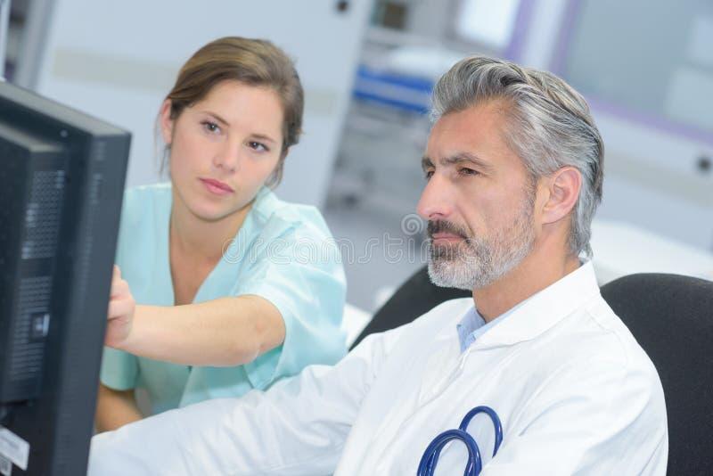 Доктор и медсестра проверяя показатели компьютера стоковые изображения