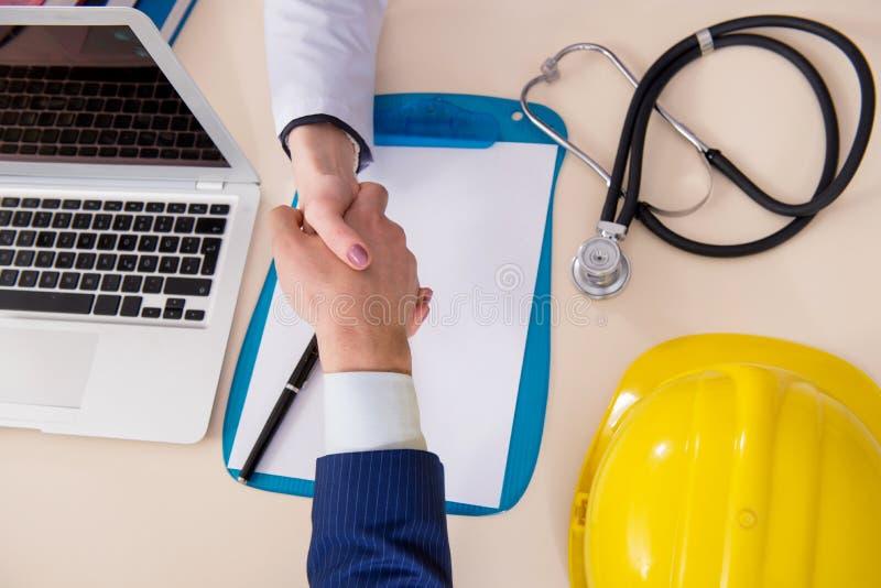 Доктор и менеджер соглашаясь страховой платеж страхования от простоя производства стоковое фото
