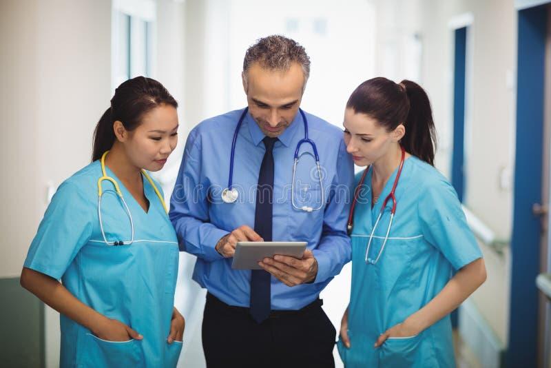 Доктор и медсестры обсуждая над цифровой таблеткой стоковые фотографии rf