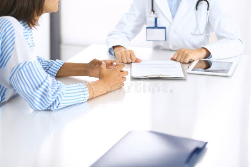 Доктор и пациент говоря и обсуждая обработку здоровья пока сидящ на столе, конце-вверх микстура здоровья внимательности стоковые изображения