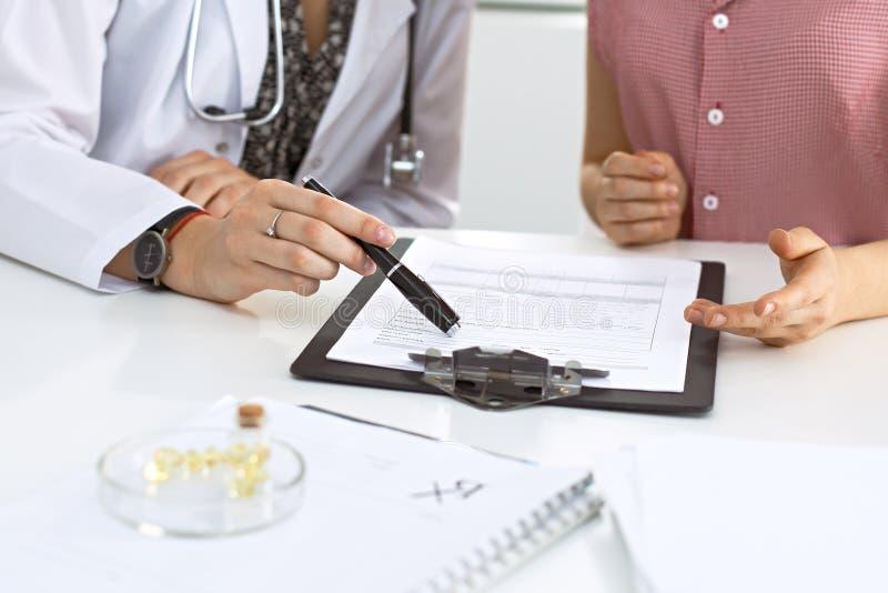 Доктор и пациент сидя на столе Врач указывая в показатели истории болезни и объясняя что-то к стоковые фотографии rf