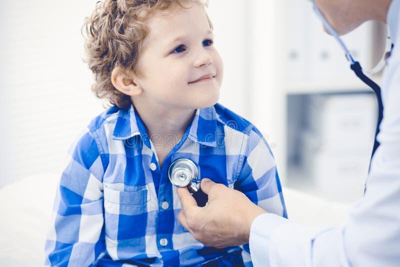 Доктор и терпеливый ребенок Мальчик врача рассматривая Регулярное медицинское посещение в клинике Медицина и здравоохранение стоковая фотография