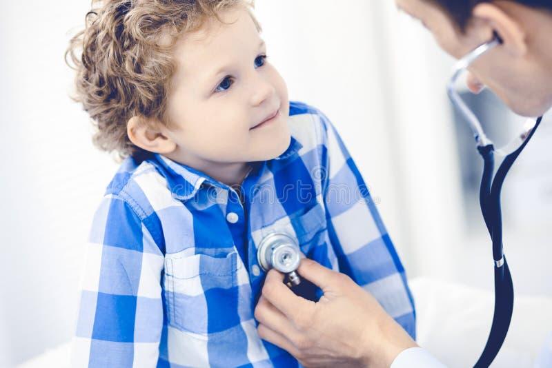 Доктор и терпеливый ребенок Мальчик врача рассматривая Регулярное медицинское посещение в клинике Медицина и здравоохранение стоковые фото
