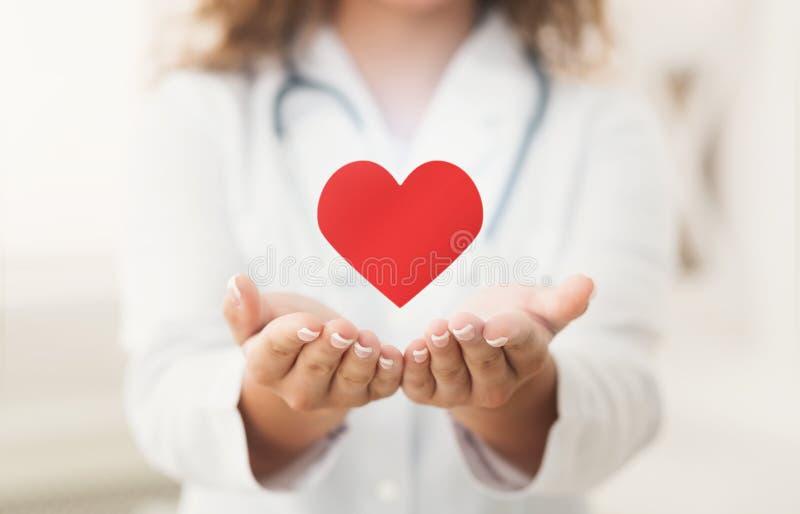 Доктор кардиолога держа виртуальное сердце в руках стоковое фото