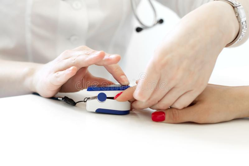 Доктор кладет дальше датчик измеряя ИМП ульс и кислород в кровь на палец пациента стоковое фото rf