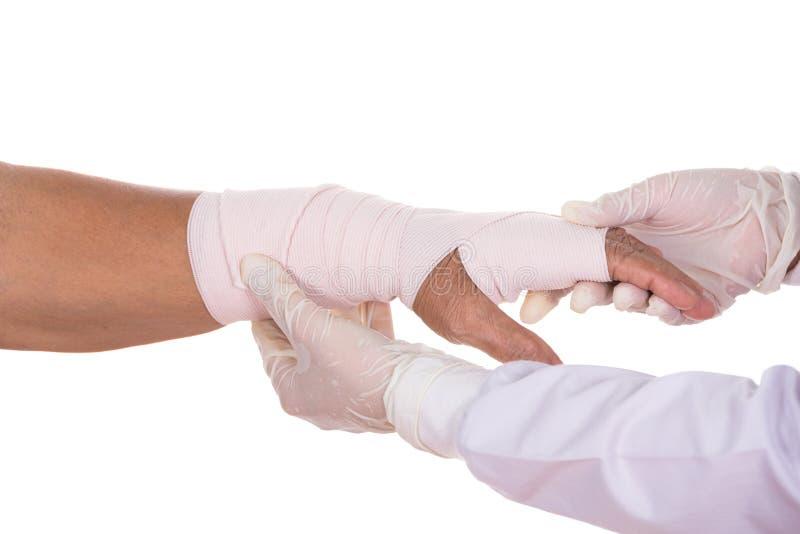 Доктор конца-вверх женский перевязывает руку пациента стоковая фотография rf