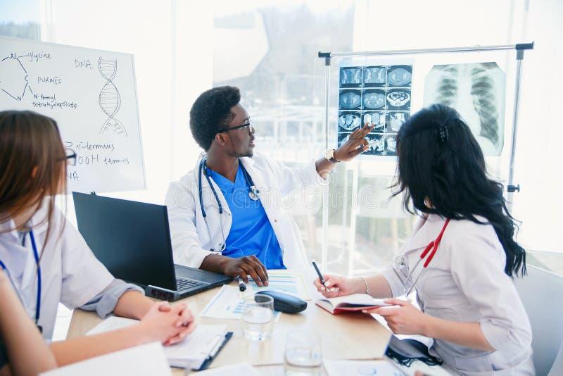 Доктор молодого Афро американский показывает результат пациента mri и обсуждает его с командой Интернациональная бригада 5 стоковое фото rf