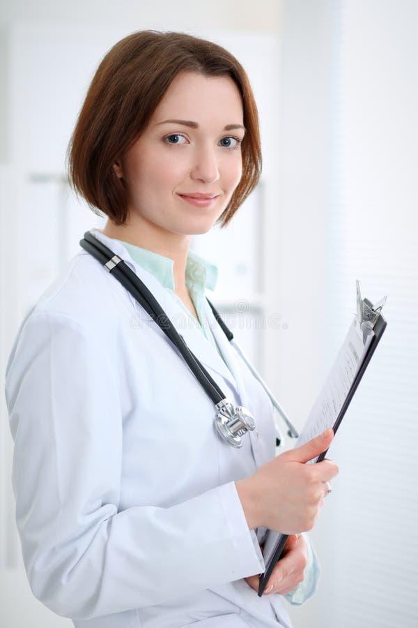 Доктор молодого брюнет женский стоя с доской сзажимом для бумаги и усмехаясь в больнице стоковые изображения