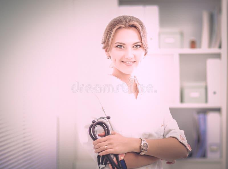 Доктор молодой женщины стоя на больнице с медицинским стетоскопом стоковые фотографии rf