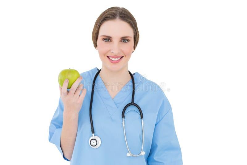 Доктор молодой женщины держа зеленое яблоко стоковое изображение