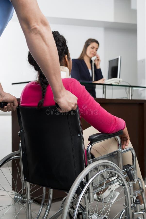Доктор Нажатие Пациент На Кресло-коляска пока деятельность работник службы рисепшн стоковая фотография rf
