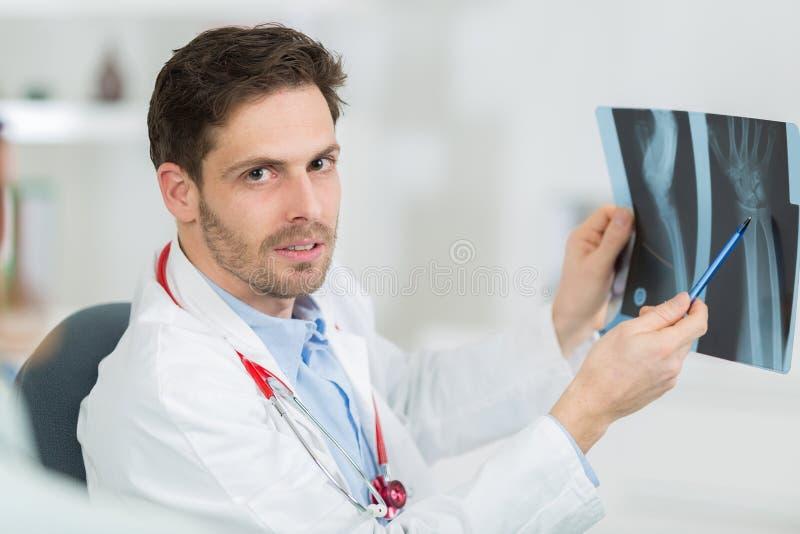 Доктор на столе держа и рассматривая рентгеновский снимок травмы стоковые изображения rf