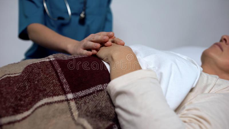 Доктор поддерживая смертельно женщину беды, надлежащую внимательность людей в доме престарелых стоковые фото