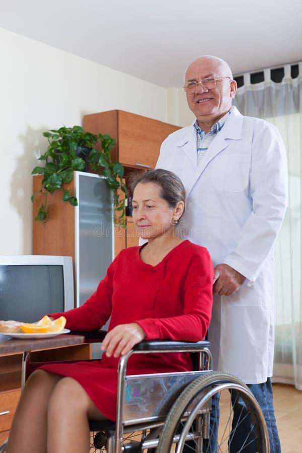 Доктор позаботится о женщина в кресло-коляске стоковые изображения