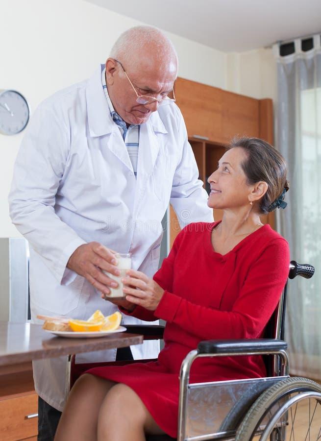 Доктор позаботить о женщина в кресло-коляске стоковое фото rf