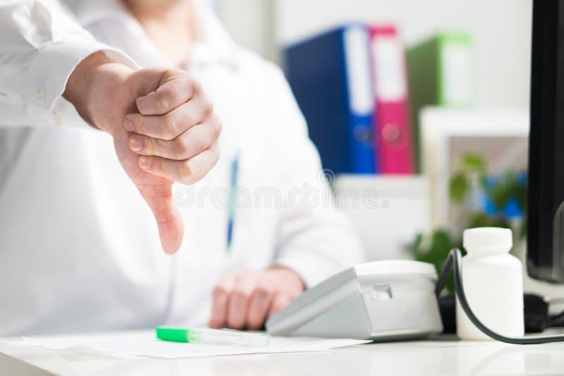Доктор показывает большие пальцы руки вниз Унылый или разочарованный doc, сотрудник военно-медицинской службы, медсестра стоковое фото rf