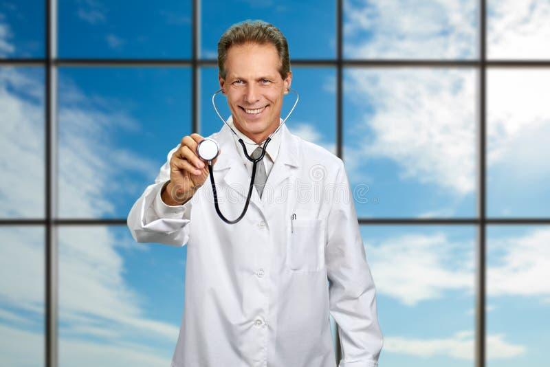 Доктор показывая стетоскоп на предпосылке неба стоковое изображение