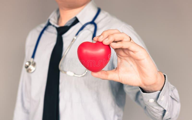 Доктор при вскользь носка и рука держа сердце стоковые изображения rf