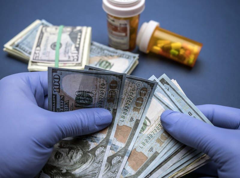 Доктор при голубые перчатки латекса подсчитывая 100 долларовых банкнот в a стоковые изображения