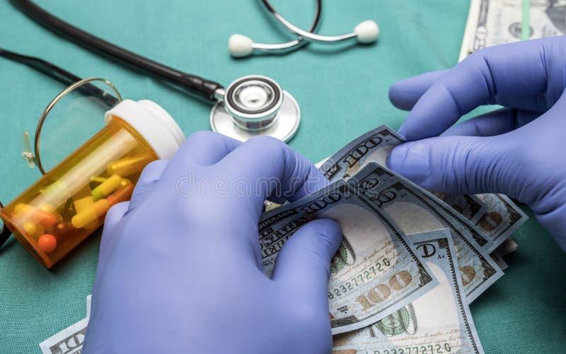 Доктор при голубые перчатки латекса подсчитывая 100 долларовых банкнот стоковая фотография