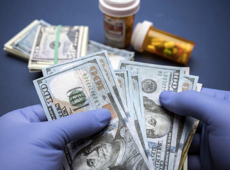 Доктор при голубые перчатки латекса подсчитывая 100 долларовых банкнот стоковые изображения rf
