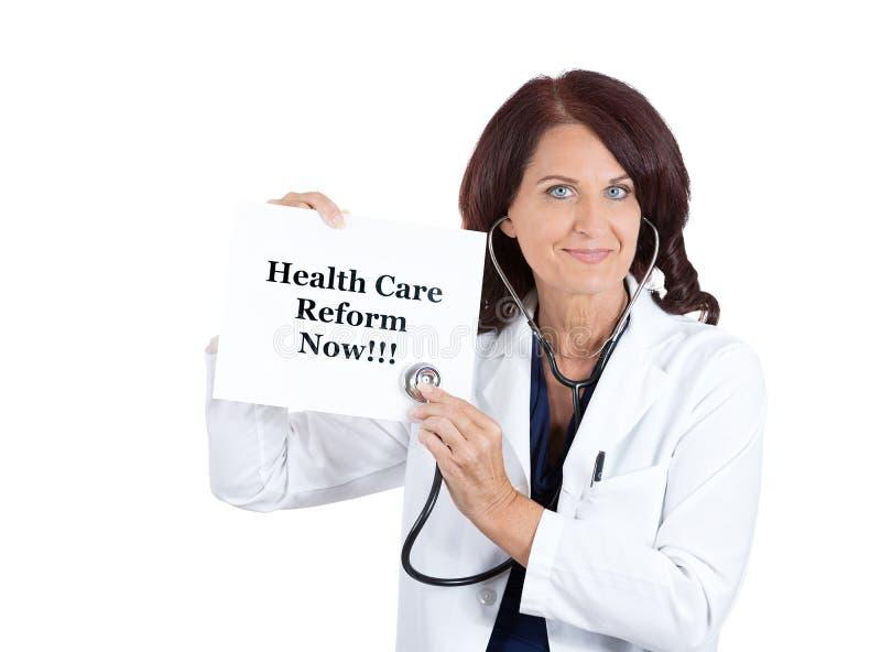 Доктор при стетоскоп держа реформу здравоохранения теперь подписывает стоковое изображение