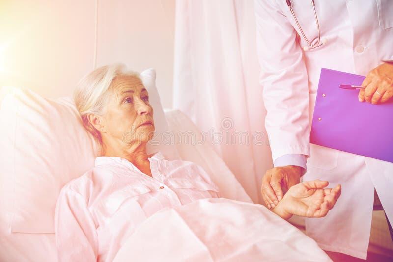 Доктор проверяя старший ИМП ульс женщины на больнице стоковая фотография