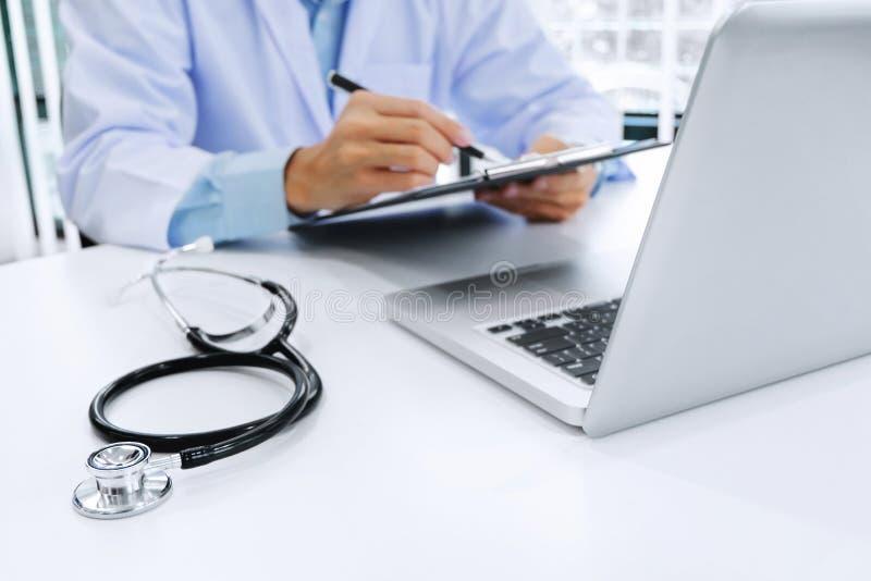 Доктор работая на ноутбуке с доской сзажимом для бумаги стетоскопа и бумаги, выборочным фокусом стоковые изображения rf