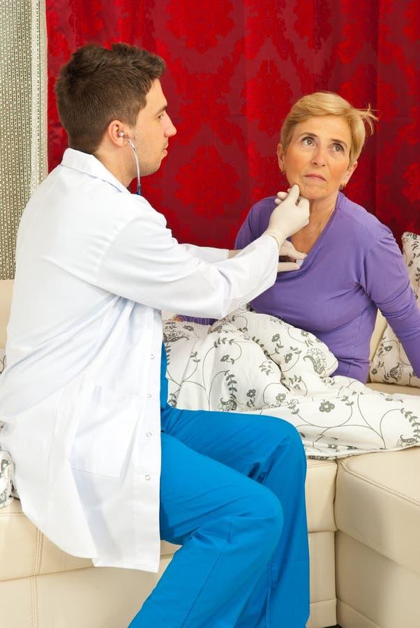 доктор рассматривает домашнюю старшую женщину стоковое изображение