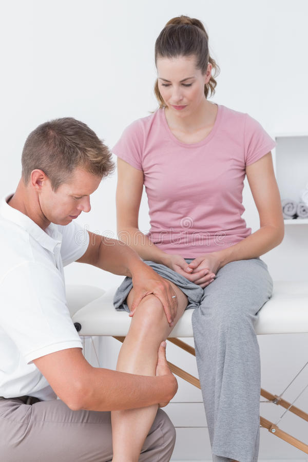 Доктор рассматривая его терпеливое колено стоковая фотография