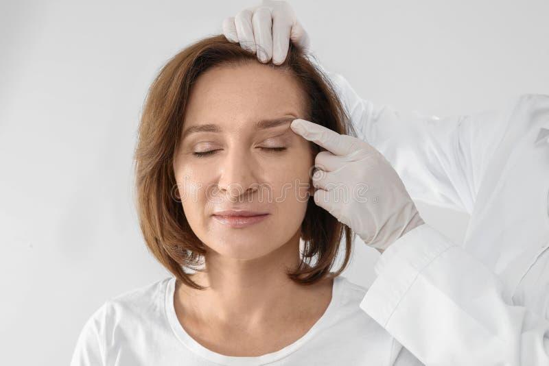 Доктор рассматривая зрелую сторону женщины перед хирургией на белой предпосылке стоковые изображения
