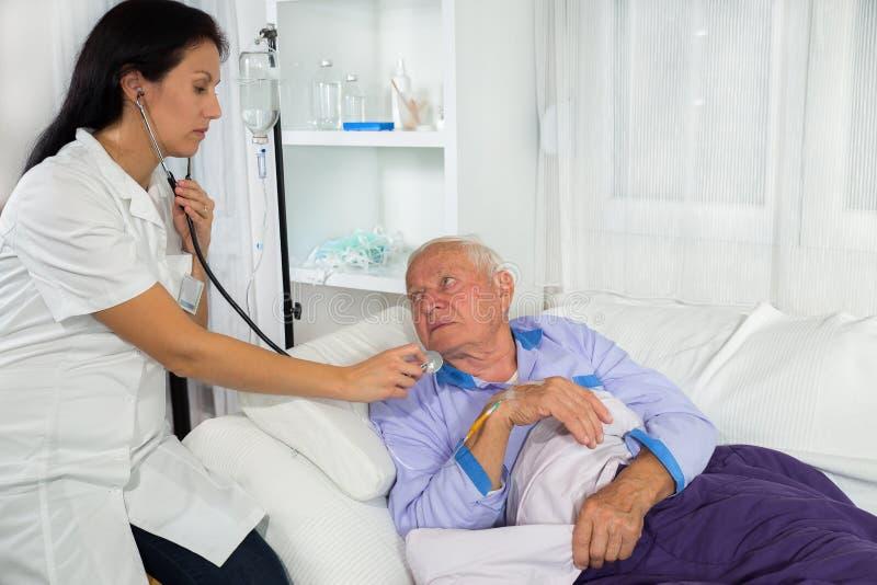 Доктор рассматривая пациента в больничной койке стоковые фото