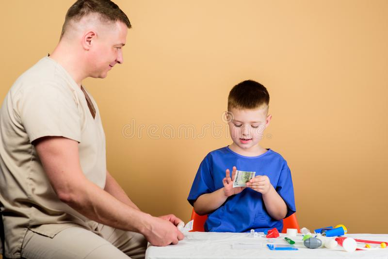 Доктор ребенк маленький сидит инструменты таблицы медицинские r r Зарплата работника больницы Ребенок мальчика милый стоковые фотографии rf
