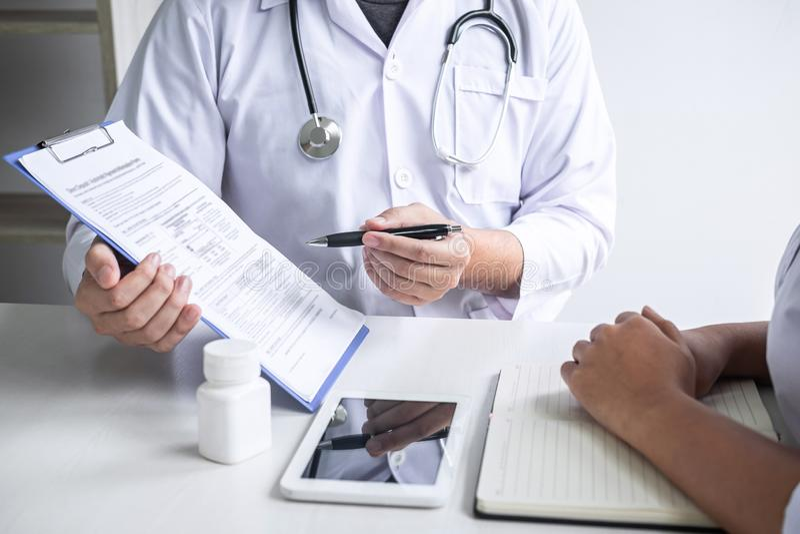 Доктор советуя с с пациентом и проверяя условие болезни пока представляющ симптом диагноза результатов рассматривая о стоковое фото rf