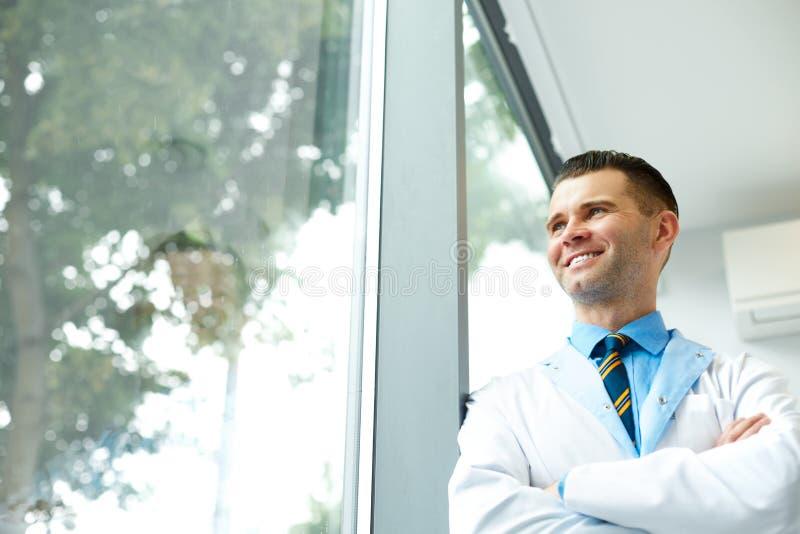 Доктор Стоять Близко Окно дантиста и думает о будущем клиники стоковая фотография rf