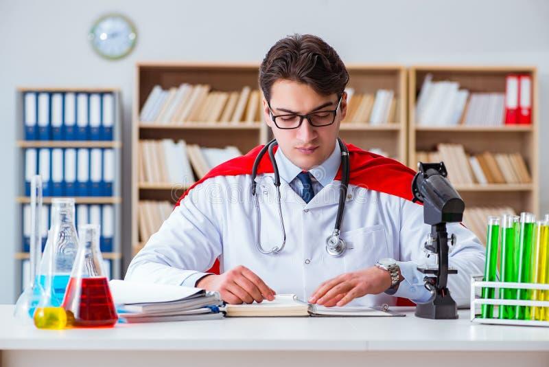 Доктор супергероя работая в лаборатории больницы стоковые изображения