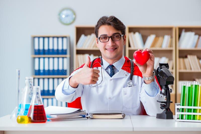 Доктор супергероя работая в лаборатории больницы стоковая фотография
