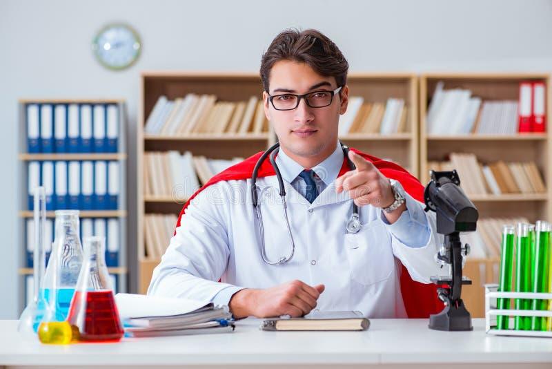 Доктор супергероя работая в лаборатории больницы стоковое изображение rf